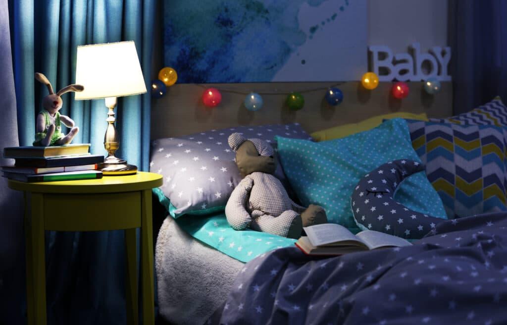 Ein Bär liegt im Bett und wartet darauf, dass eine Gute-Nacht-Geschichte vorgelesen wird.